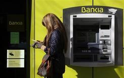 Bankia prevé anunciar este jueves unas pérdidas algo superiores a 19.000 millones de euros para 2012 enmarcadas en el plan de recapitalización europeo a la espera de que el FROB anuncie la valoración para la ampliación de capital que reducirá casi a cero el valor de los accionistas actuales. Imagen de una mujer en uncajero de Bankia en Madrid el 15 de febrero. REUTERS/Sergio Pérez