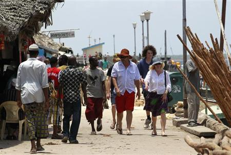 Tourists walk on the shores of the Indian Ocean in the Kenyan coastal town of Lamu, October 2, 2011. REUTERS/Thomas Mukoya