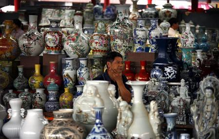 A vendor sits amongst his collection of ceramics as he waits for customers at a small market in central Beijing September 8, 2012. REUTERS/David Gray
