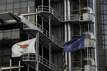 An EU and a Cyprus flag flutter in front of Laiki Bank's headquarters in Nicosia February 21, 2013. REUTERS/Yorgos Karahalis