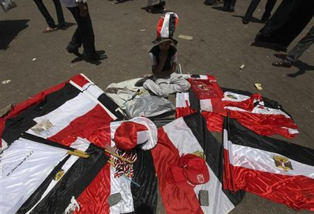 A street vendor sits next to Egyptian flags for sale during a demonstration against the verdict for deposed leader Hosni Mubarak, and against presidential candidate and former prime minister Ahmed Shafiq at Tahrir Square in Cairo June 5, 2012. REUTERS/Amr Abdallah Dalsh