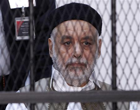 Baghdadi al-Mahmoudi, who was the last prime minister of Muammar Gaddafi's government, sits behind bars during the second hearing in his trial at a prison facility in Tripoli December 10, 2012. REUTERS/Ismail Zitouny