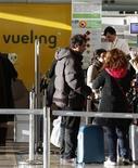 La aerolínea Vueling dijo el miércoles que cerró 2012 con un beneficio neto de 28,3 millones de euros, una mejora del 173 por ciento sobre el resultado de 2011, al tiempo que la opa anunciada por IAG está retrasando la renovación de su flota. En la imagen, unos pasajeros esperan para facturar con Vueling el 30 de enero de 2012 en Barcelona. REUTERS/Gustau Nacarino