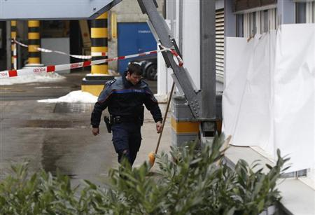 A police officer walks past covered windows in the wood processing plant of Kronospan following a shooting in Menznau near Lucerne February 27, 2013. Three people, including the suspected assailant, have been killed in a shooting at a factory near the Swiss city of Lucerne, police said on Wednesday. Seven others were injured in the attack which happened just after 9 a.m. (0800 GMT) at a wood processing company in the town of Menznau, west of Lucerne, the police said in a statement. REUTERS/Michael Buholzer (SWITZERLAND - Tags: CRIME LAW) - RTR3ECRJ