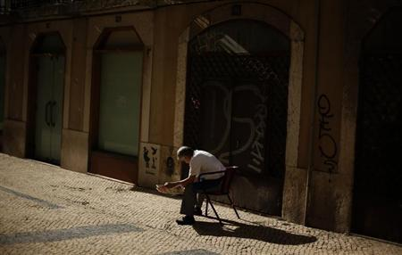A man reads a newspaper in downtown Lisbon January 23, 2013. REUTERS/Rafael Marchante