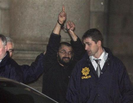 Ali Charaf Damache, also known by the alias ''Black Flag,'' is accompanied by Irish law enforcement officials as he appears at Waterford District Court to be remanded into custody after being arrested on terrorism charges in Waterford, Ireland in this March 13, 2010 file photo. REUTERS/Patrick Browne/Files