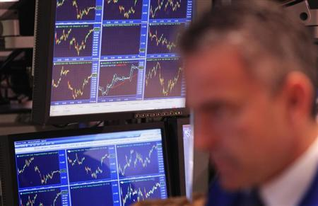 Price charts are displayed on a screen behind a trader as he works on the floor of the New York Stock Exchange after the closing bell in New York November 11, 2011. REUTERS/Lucas Jackson