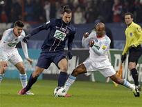 Duel entre le Parisien Zlatan Ibrahimovic et le Marseillais Andre Ayew (à droite). Le Paris Saint-Germain a battu l'Olympique de Marseille pour la deuxième fois en trois jours mercredi en huitièmes de finale de la Coupe de France, sur le même score que dimanche en Ligue 1 (2-0) et a rejoint Lorient, Bordeaux et Nancy en quarts. /Photo prise le 27 février 2013/REUTERS/Jacky Naegelen