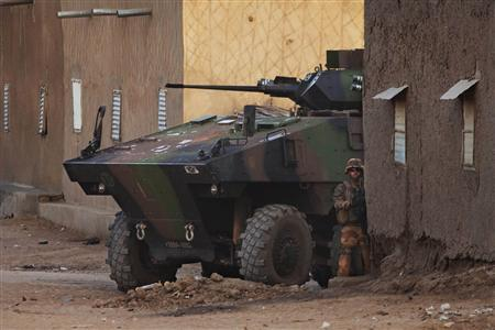 A French soldier stands next to an armoured vehicle during an operation to collect explosives found in a house in Gao February 27, 2013. REUTERS/Joe Penney