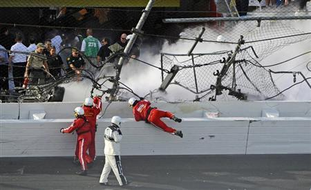 Rescue workers respond next to a hole in the catch fence following a last-lap incident during the NASCAR Nationwide Series DRIVE4COPD 300 race at the Daytona International Speedway in Daytona Beach, Florida February 23, 2013. REUTERS/Brian Blanco