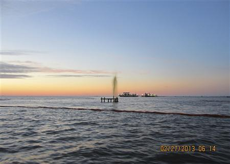 An inactive wellhead owned by Swift Energy is seen discharging an oily-watery mixture after being struck by a 42-foot crewboat, the Sea Rider, off the coast of Port Sulphur, Louisiana February 26, 2013 in this U.S. Coast Guard handout photo released February 27, 2013. REUTERS/U.S. Coast Guard/Handout