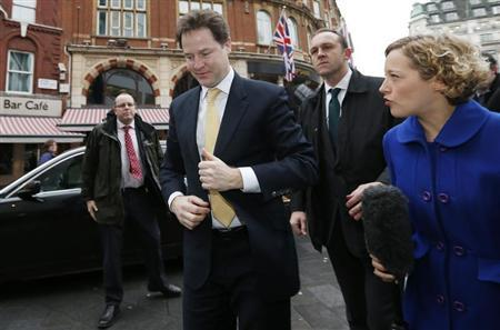 Britain's deputy Prime Minister Nick Clegg (2nd L) arrives to take part in a phone-in show at a radio station in central London February 27, 2013. REUTERS/Suzanne Plunkett