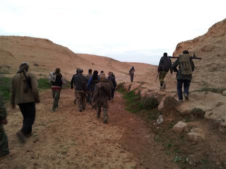 Members of the Free Syrian Army walk with their weapons in Deir el-Zor February 26, 2013. Picture taken February 26, 2013. REUTERS/Ammar Iessa /Shaam News Network/Handout