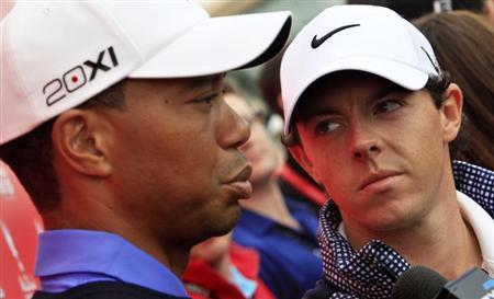 Rory McIlroy of Northern Ireland (R) looks at Tiger Woods of the U.S. during an interview ahead of the Abu Dhabi Golf Championships January 15, 2013. REUTERS/Ahmed Jadallah/Files