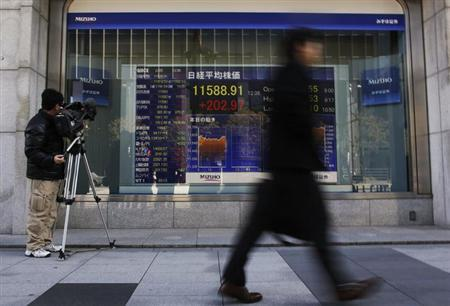 A man walks past a stock index board as a television cameraman films outside a brokerage in Tokyo February 25, 2013. REUTERS/Yuya Shino