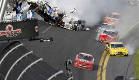 NASCAR driver Tony Stewart (bottom R) avoids a crash on the last lap to win the NASCAR Nationwide Series DRIVE4COPD 300 race at the Daytona International Speedway in Daytona Beach, Florida February 23, 2013. REUTERS/Michael Brown