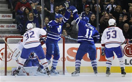 Toronto Maple Leafs' Frazer McLaren (2nd L) celebrates his goal with teammate Jay McClement (2nd R) in front of Montreal Canadiens' Travis Moen (L) and Ryan White during the first period of their NHL hockey game in Toronto February 27, 2013. REUTERS/Mark Blinch