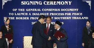 Secretary-general of Thailand's National Security Council, Paradorn Pattanathabutr (centre L), shakes hands with chief of Thailand's National Revolution Front (BRN) liason office in Malaysia, Hassan Taib (centre R), as they exchange documents during the signing ceremony of the general consensus document to launch a dialogue process for peace in the border provinces of southern Thailand, in Kuala Lumpur February 28, 2013. REUTERS/Bazuki Muhammad