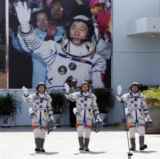 Chinese astronauts Jing Haipeng (C), Liu Wang (R) and Liu Yang, China's first female astronaut, wave in front of a picture of the first astronaut Yang Liwei during a departure ceremony at Jiuquan Satellite Launch Center, Gansu province, June 16, 2012. REUTERS/Jason Lee