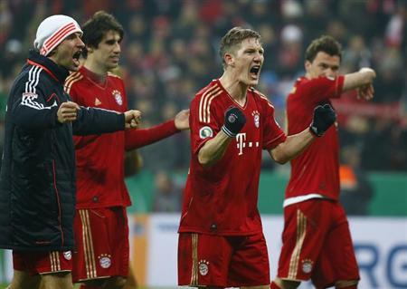 Bayern Munich players celebrate their 1-0 victory over Borussia Dortmund with the team's mascot following their German soccer cup, DFB Pokal, quarter final match in Munich February 27, 2013. REUTERS/Michaela Rehle
