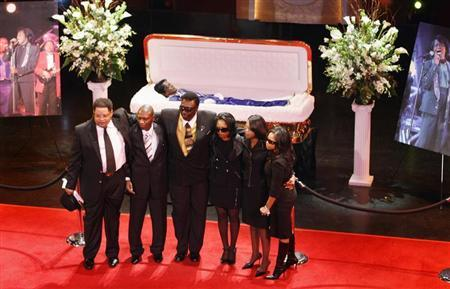 Members of singer James Brown's family stand in front of Brown's coffin during a public viewing at the Apollo Theater in New York December 28, 2006. REUTERS/Lucas Jackson