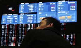 Мужчина изучает котировки на информационном табло Токийской фондовой биржи 6 февраля 2013 года. Азиатские фондовые рынки выросли в четверг после выступления главы ФРС в Конгрессе и успешного аукциона облигаций Италии. REUTERS/Toru Hanai