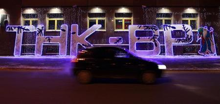 A car drives past an illuminated sign displayed in front of the local office of TNK-BP company in the Siberian city of Tyumen, January 17, 2013. REUTERS/Eduard Korniyenko