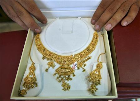 A shopkeeper displays gold jewellery inside his showroom in Jammu September 15, 2008. REUTERS/Amit Gupta/Files