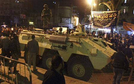 Protesters opposing Egyptian President Mohamed Mursi gather near a military tank as they take part in a march despite a nighttime curfew in the city of Suez in this January 28, 2013 file picture. To match Insight EGYPT-ARMY REUTERS/Stringer/Files
