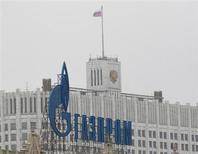 Логотип Газпрома на фоне Белого дома в Москве 8 февраля 2013 года. Министерство экономики РФ ожидает 10-процентного падения мировых цен на газ, но готово лишить Газпром части доходов на внутреннем рынке, чтобы не разгонять инфляцию, сказал в четверг замглавы Минэкономики Андрей Клепач. REUTERS/Maxim Shemetov