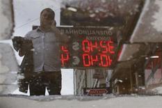 """Отражение в луже мужчины, стоящего у пункта обмена валют в Москве 8 июня 2012 года. Рубль торгуется с минимальным преимуществом к бивалютной корзине на спокойной биржевой сессии четверга - отыграть рост рискованных активов после """"голубиных"""" комментариев главы ФРС Бена Бернанке ему мешали дешевая нефть и локальный спрос на валюту США, но продаж экспортной выручки пока достаточно для баланса сил на валютной рынке. REUTERS/Maxim Shemetov"""