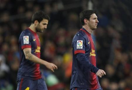 Barcelona's Lionel Messi (R) and Cesc Fabregas leaves the pitch after their Spanish King's Cup semifinal second round soccer match against Real Madrid at Camp Nou stadium in Barcelona February 26, 2013. REUTERS/Gustau Nacarino