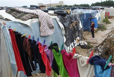 A Syrian girl looks on as clothes are left hanging on a line at a refugee camp in the city of Tyre, in southern Lebanon, January 31, 2013. REUTERS/Ali Hashisho