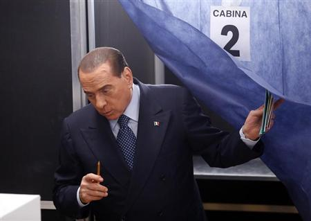 Former Prime Minister Silvio Berlusconi leaves a polling booth after casting his vote in Milan February 24, 2013. REUTERS/Stefano Rellandini