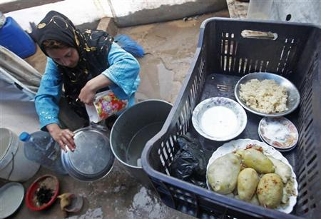 A Syrian woman washes dishes at a refugee camp in the city of Tyre, in southern Lebanon January 31, 2013. REUTERS/Ali Hashisho