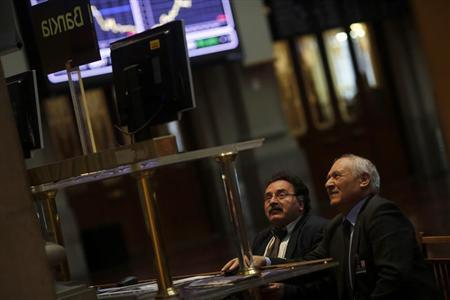 A trader looks at computer screens next to a Bankia sign at Madrid's stock exchange February 28, 2013. REUTERS/Susana Vera