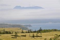 Действующий вулкан Менделеева или Rausu-yama возвышается над островом Кунашир Курильской гряды 18 июня 2008 года. Подземный толчок магнитудой семь баллов произошел в четверг на юге Камчатки, вблизи Курильских островов, на глубине 30 километров, сообщила Геологическая служба США (USGS). REUTERS/Yuri Maltsev