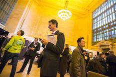 El número de estadounidenses que solicitó un subsidio de desempleo bajó más de lo esperado la semana pasada, lo que sugiere cierto impulso en la recuperación del mercado laboral. En la imagen, un aspirante consulta su teléfono móvil mientras espera a hablar con reclutadores en una feria de empleo de la empresa The Ladders en la Grand Central Station de Nueva York, el 10 de enero de 2013. REUTERS/Lucas Jackson