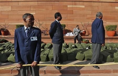 Security personnel stand guard near sacks containing the 2013/14 federal budget papers at the parliament in New Delhi February 28, 2013. REUTERS/Adnan Abidi