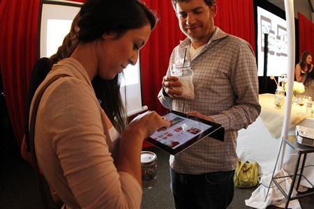 People interact with a Pinterest app on a tablet device during a launch party, August 14, 2012. REUTERS/Pinterest/Handout
