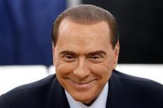 Imagen de archivo del ex primer ministro italiano Silvio Berlusconi tras votas en las elecciones en Milán, feb 24 2013. El ex primer ministro italiano Silvio Berlusconi, que intenta nuevamente llegar al Gobierno tras las últimas elecciones, fue puesto bajo investigación por sospechas de sobornar a un senador para que se cambiara de partido en el 2006, dijeron el jueves fuentes de la investigación. REUTERS/Stefano Rellandini