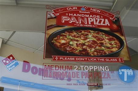 A poster for Domino's Hand Made Pan Pizza is displayed in a window of a Domino's pizza restaurant in Burbank, California October 16, 2012. REUTERS/Fred Prouser
