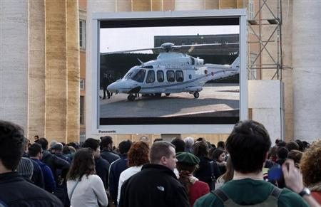 People in Saint Peter's Square in the Vatican City watch a giant screen of the helicopter waiting to carry Pope Benedict XVI to the papal summer residence at Castelgandolfo, February 28, 2013. REUTERS/Stefano Rellandini