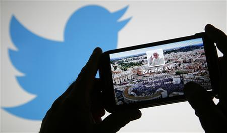Pope Benedict XVI's twitter account is pictured on a smart phone in front of the Twitter logo displayed on a laptop in this photo illustration taken in Rome December 3, 2012. REUTERS/Max Rossi