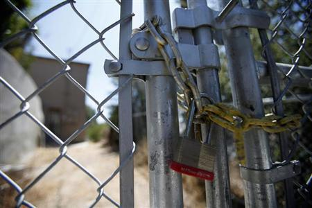 A lock secures a chain on the steel fence of a foreclosed home previously owned by U.S. Bancorp in Los Angeles, California July 17, 2012. REUTERS/Mario Anzuoni