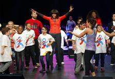 U.S. first lady Michelle Obama dances on stage with school children during an event to bring physical activity back to schools, hosted by the American Alliance for Health, Physical Education, Recreation and Dance (AAHPERD) and the Alliance for a Healthier Generation in Chicago, Illinois, February 28, 2013. REUTERS/Jeff Haynes