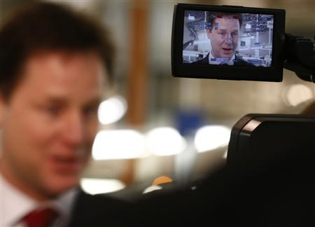 Britain's Deputy Prime Minister Nick Clegg is seen in a camera viewfinder as he speaks to members of the media at the Aston Martin production facility in Gaydon, central England February 28, 2013. REUTERS/Darren Staples