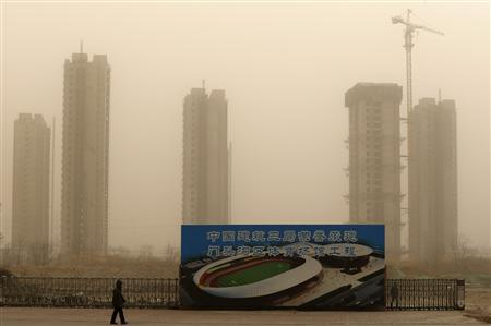 A man walks past a construction site for a new stadium in Mentougou district, suburb of Beijing February 28, 2013. REUTERS/Kim Kyung-Hoon