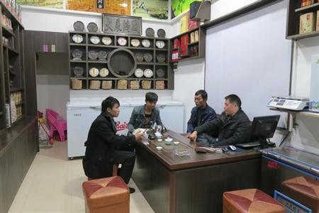 Zhuang Liehong (R), a former protest leader, chats with friends in his new tea shop on the main street Wukan village, Guangdong province December 4, 2012. REUTERS/James Pomfret/Files