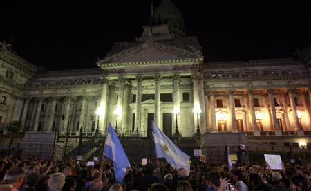 People wave Argentine flags as they attend a demonstration to protest against an agreement between Argentina and Iran outside the Argentine Congress in Buenos Aires February 27, 2013. REUTERS/Marcos Brindicci